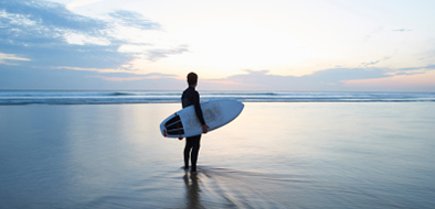 Person standing on the beach with surfing board